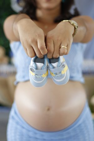 A pregnant lady holding a pair of newborn baby's shoes n front of her.