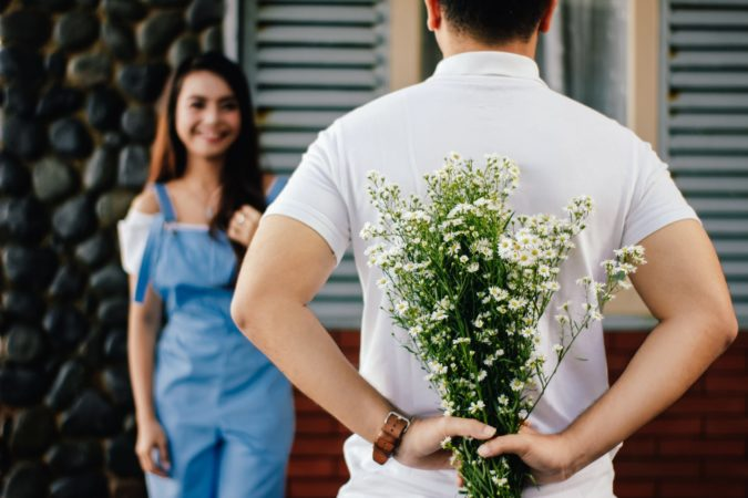 A man holding flowers behind his back while a lady greets him.