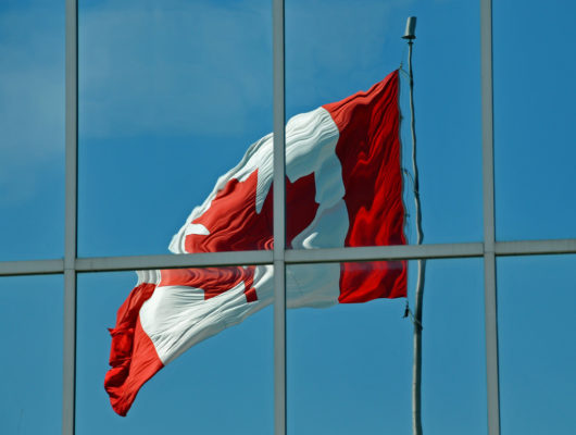The reflection of the Canadian flag in the windows of an office building.