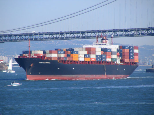 A shipping vessel passing under a bridge.