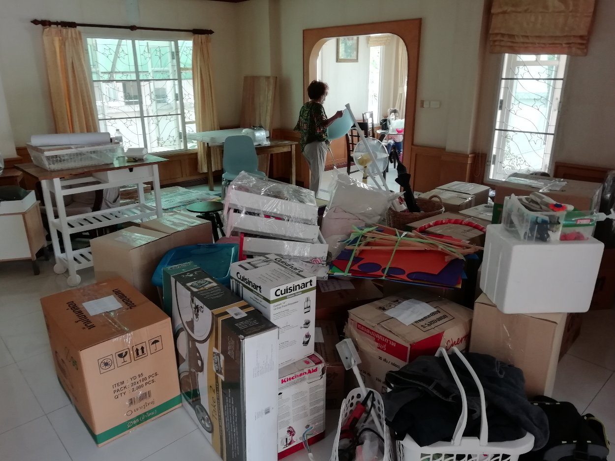 A room full of packed moving boxes and furniture.