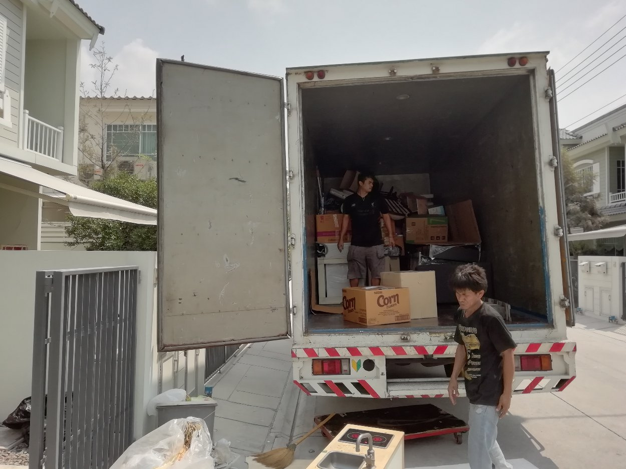 Movers loading a moving truck with boxes and furniture.