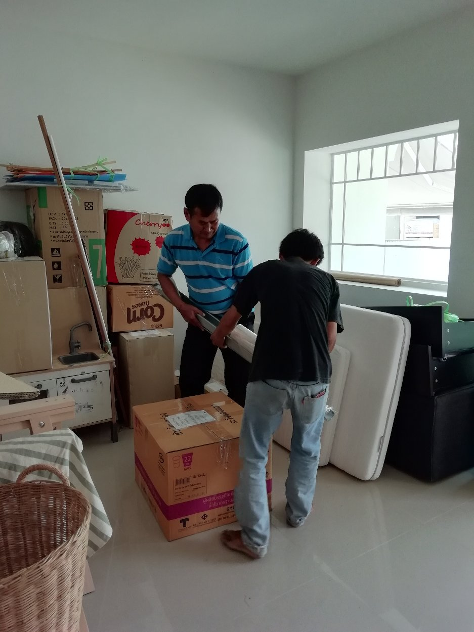Movers wrapping a box with plastic in a living room.