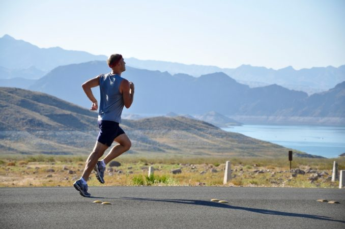 A man running down the road with a lake and some mountains behind him.