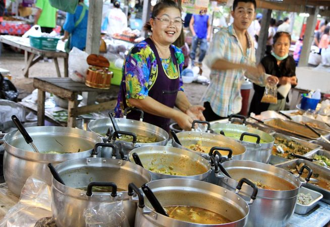A Thai lady serving food at a street food stand in Thailand.
