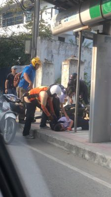 A motorcycle taxi driver tending to a student he hit with his motorbike..