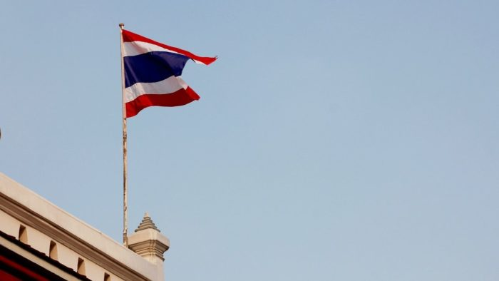 A Thai flag flying above a building.