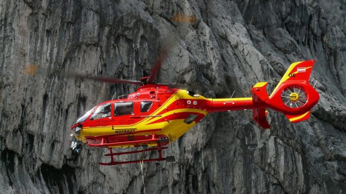 A medical helicopter in the foregroud of some mountains.
